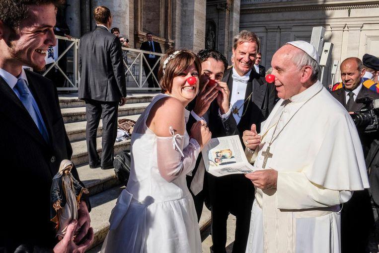 Paus Franciscus grapt met een pasgetrouwd stel dat werkt bij een Italiaanse organisatie die clowntherapie aanbiedt in ziekenhuizen en weeshuizen, Vaticaanstad, november 2013. Beeld Alamy
