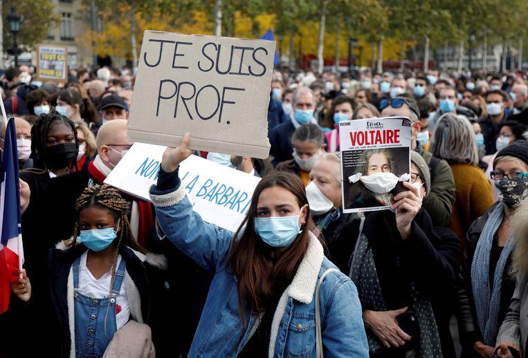 Mensen brengen hulde aan de vermoorde leraar Samuel Paty op de  Place de la République in Parijs. Beeld REUTERS