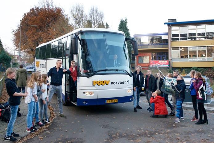 Leerlingen en teamleider Bert Mollema van de Arnhemse scholengemeenschap Guido bij bus 621.