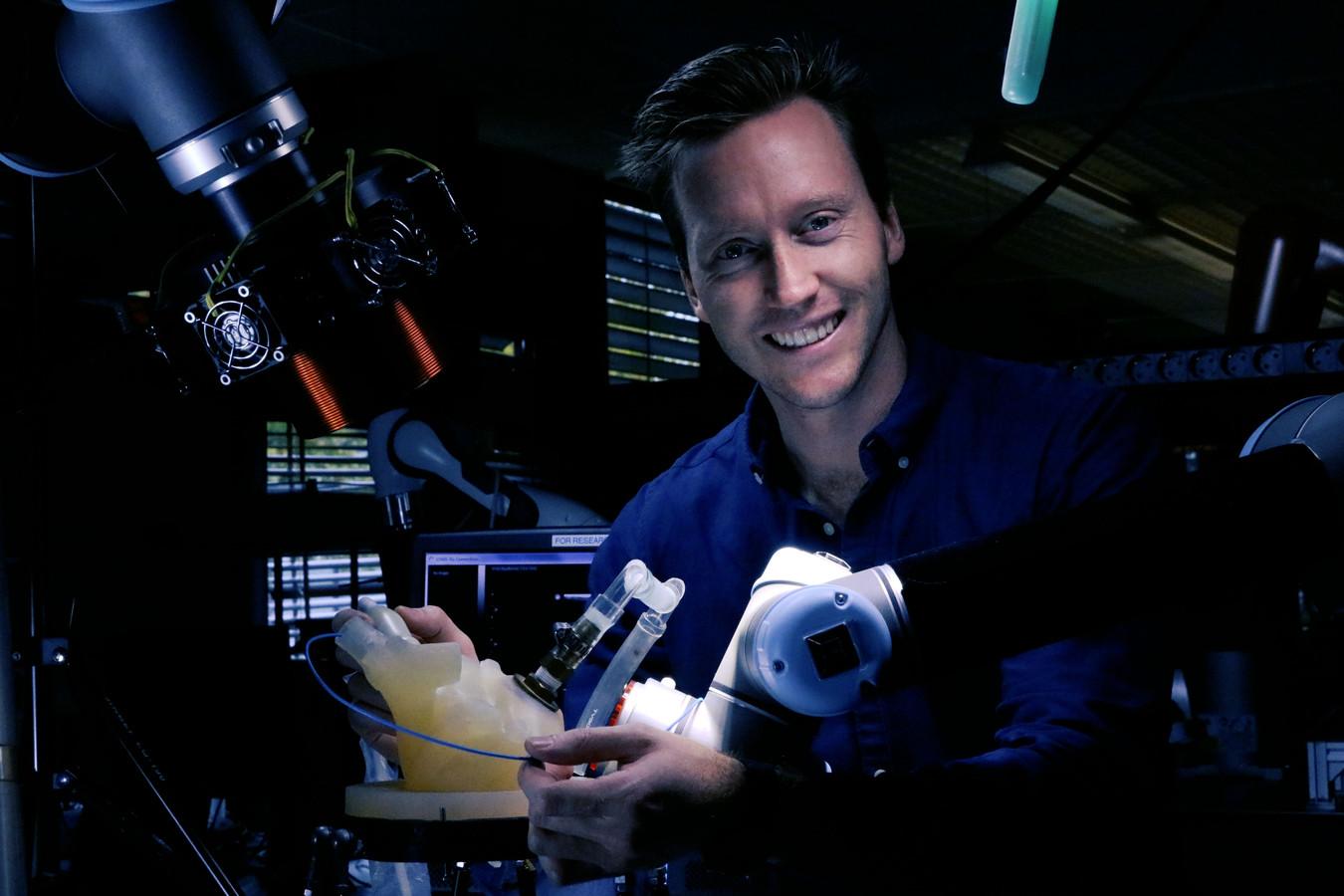 Christoff Heunis met de robotarm die de chirurg moeten bijstaan.