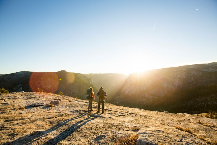 A couple standing on a high peak while backpacking in Yosemite Valley. Beeld Getty Images