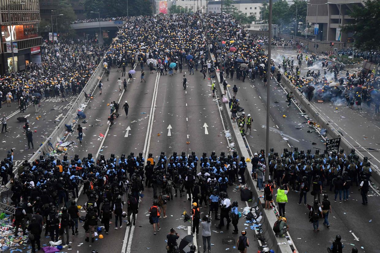Duizenden demonstranten tegenover de politie in de straten van Hongkong. Beeld Anthony Wallace / AFP