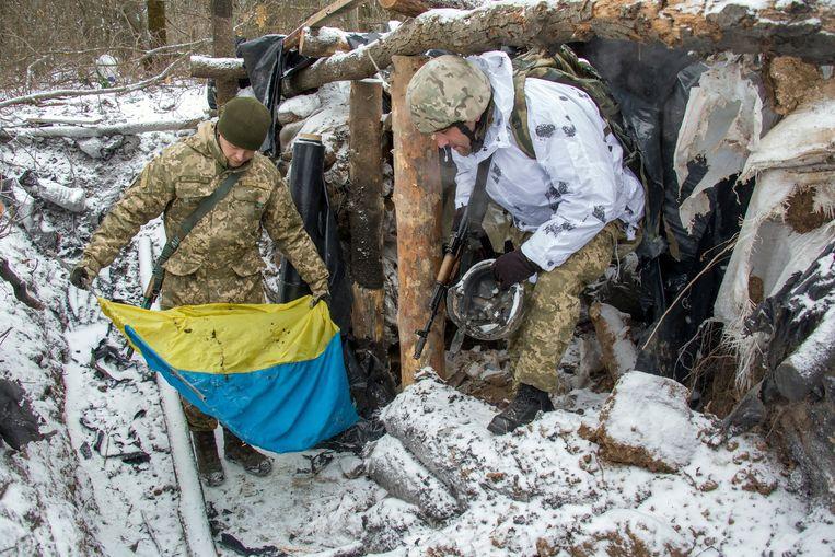 Oekraïense soldaten halen een Oekraïense vlag uit het puin van een gebombardeerde schuilplaats in Novognatovka, in het gebied Donetsk.  Beeld EPA
