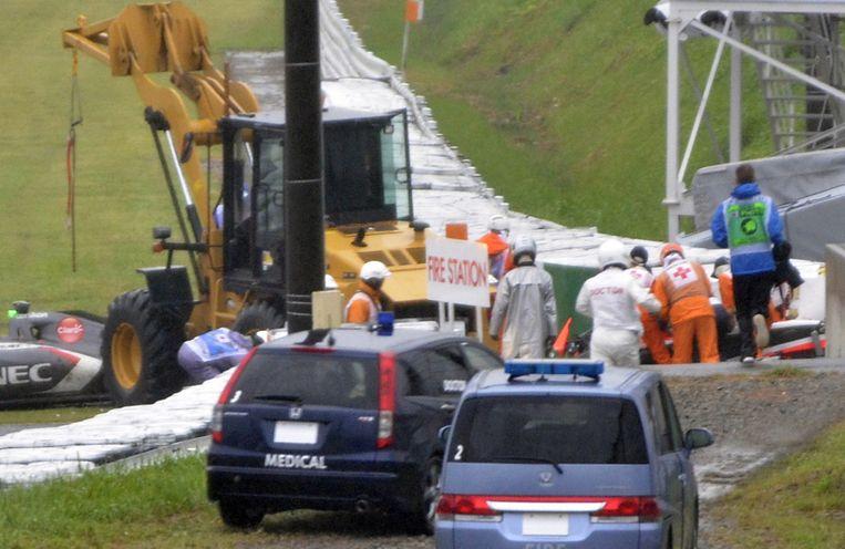 Reddingswerker bij de auto van Jules Bianchi, kort na zijn crash. Beeld ap