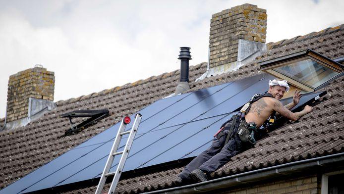 Op een woonhuis worden zonnepanelen geplaatst.