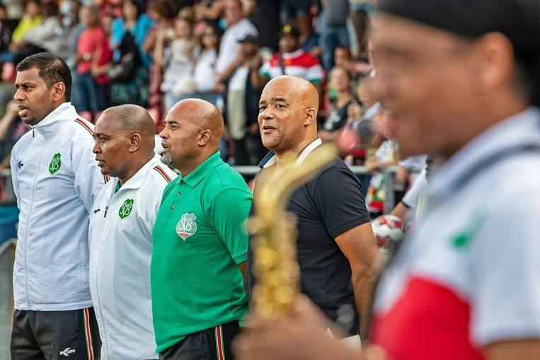 Bondscoach Dean Gorre (in het groen) zingt voorafgaand aan Telstar-Suriname mee met het Surinaams volkslied, dat gespeeld wordt door een saxofonist. Beeld null