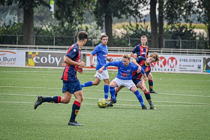 Hoeven-speler Niels Buijs (voorgrond, blauw shirt) moest eind eerste helft geblesseerd naar de kant.