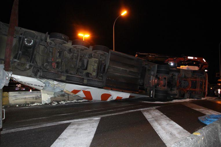 De vrachtwagen ligt op de betonnen vangrails en verspert de afrit.