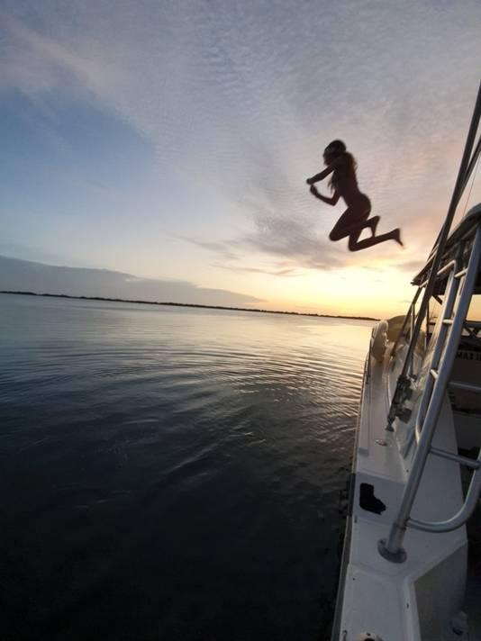 Vakantie vieren op Curaçao kan weer en Madelief Splinter springt vanaf de boot bij de ondergaande zon Fuik baai in.