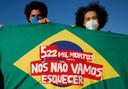 """Demonstranten houden de Braziliaanse vlag vast met de tekst: """"522.000 doden, wij zullen dat niet vergeten""""."""