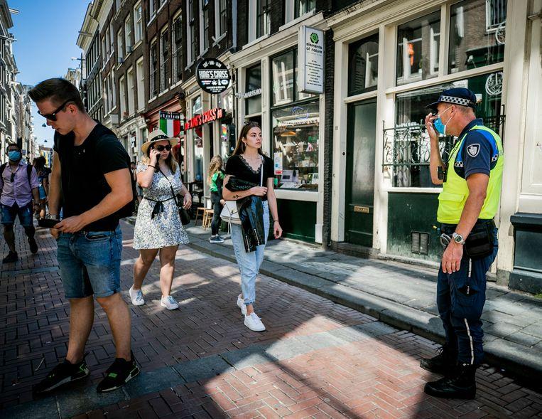 Een handhaver vraagt een toerist een mondkapje te dragen in de Warmoesstraat.  Beeld Hollandse Hoogte /  ANP