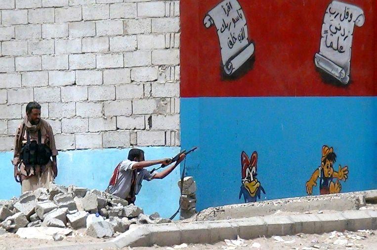 KATRIEN DUCK & PINOCCIO Een Jemenitische strijder lost een schot in de strijd tegen de Huthi-rebellen in Aden, Jemen, april 2015. Beeld afp