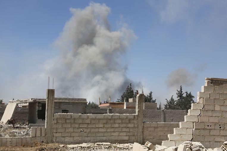 Een helikopter van de Syrische luchtmacht dropte zaterdagavond in Douma een vatenbom met chemicaliën, zo zeggen de Witte Helmen.  Beeld AFP
