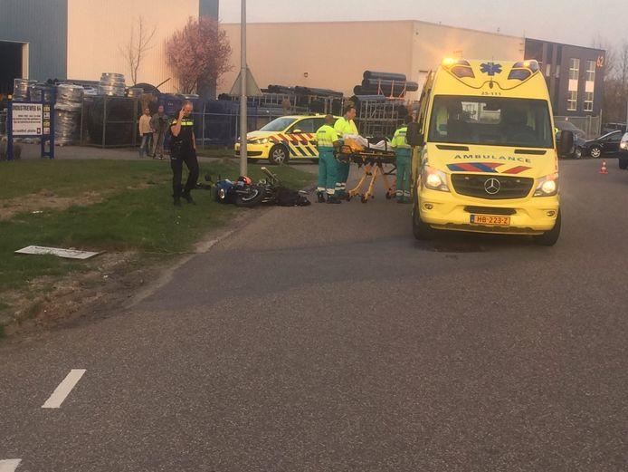 De motorrijder wordt door het ambulancepersoneel naar de ambulance gebracht.