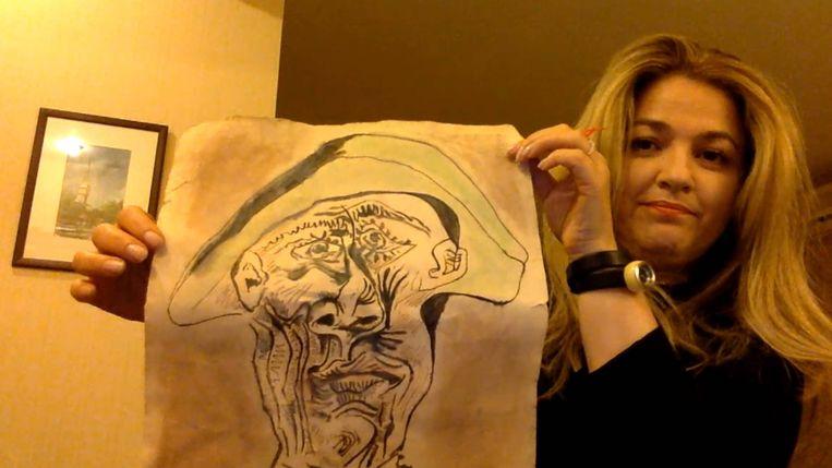 Mira Feticu toont de gevonden (nep-)Picasso aan een tv-ploeg. Beeld NOS