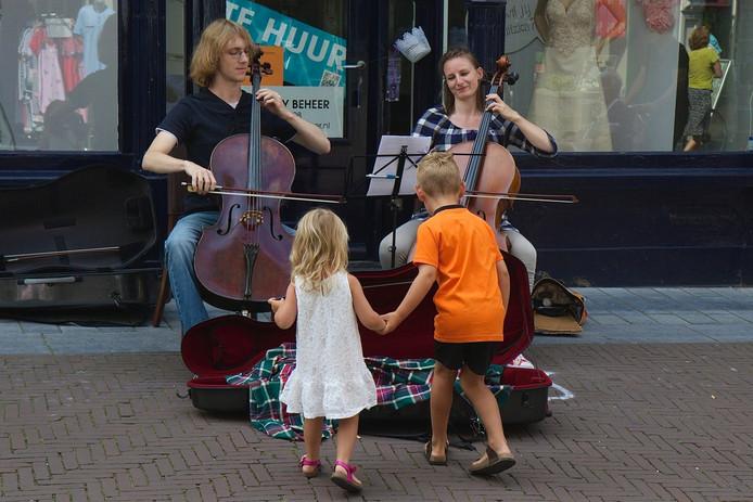 De jonge cellisten Matthijs van Niekerk en Hanne Steffers verdienen zaterdag op de Turfstraat een centje bij tijdens het Zutphense Cellofestival.