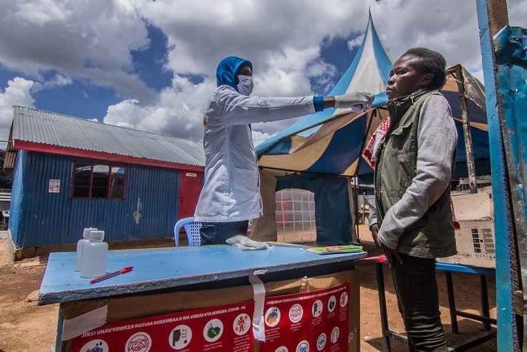 De temperatuur van een patiënt in Kenia wordt gemeten. In het land bleek ondanks heel wat besmette mensen het virus relatief weinig impact te hebben. Beeld ZUMA Press