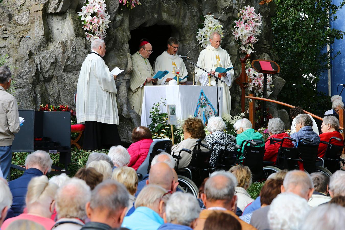 Bisschop Van den Hende (tweede van links) gaat voor in de traditionele viering ter gelegenheid van Maria-Tenhemelopneming in de Lourdesgrot in Noordeinde.