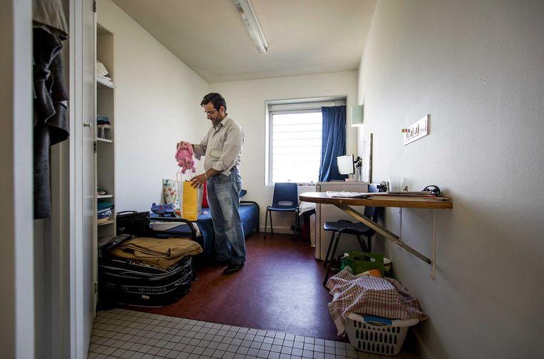 2016-09-08 15:38:38 AMSTERDAM - Een asielzoeker met cadeau's voor zijn kinderen tijdens de open dag in azc Amsterdam, de voormalige Bijlmerbajes. De voormalige gevangenis is is sinds juni gesloten en is omgebouwd tot asielzoekerscentrum. ANP KOEN VAN WEEL Beeld anp