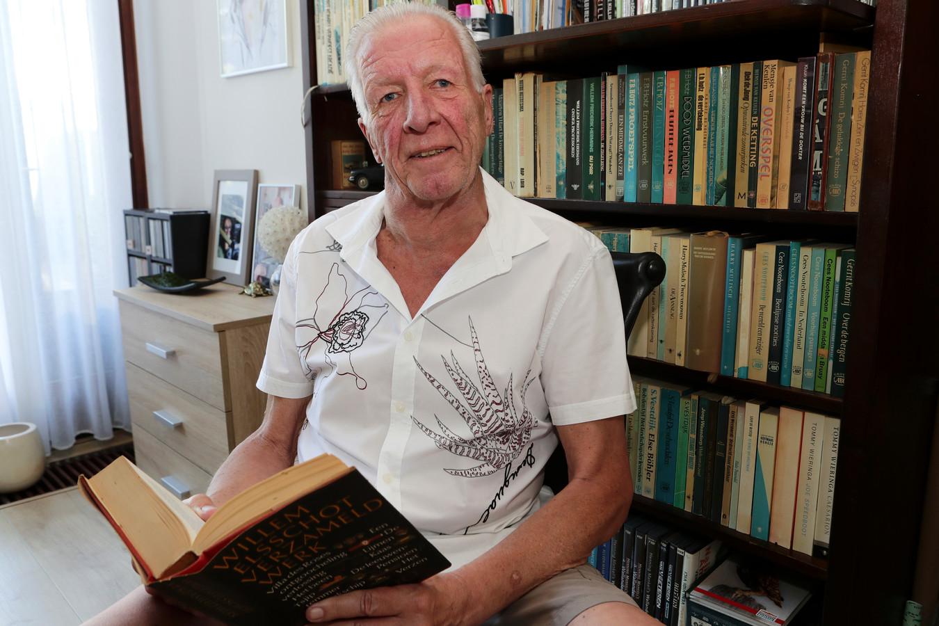 Ton Lohman (66) voor zijn boekenkast, bladerend in het verzameld werk van Willem Elsschot, zijn 'absolute favoriet'.