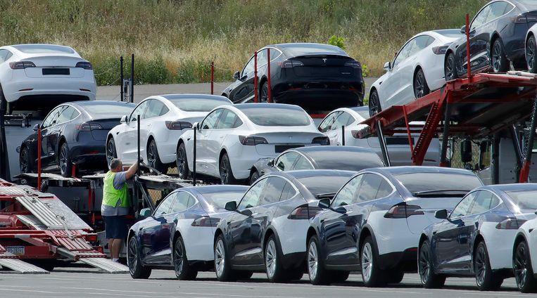 Tesla-auto's worden half mei op de vrachtwagen geladen aan de fabriek in Californië. Terwijl veel fabrieken sloten, hield Tesla de deuren langer open. Beeld AP