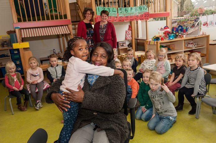 De grootmoeder van Deedee zorgt al 4 jaar in Nederland voor haar kleindochter. Op de achtergrond links directeur Clazien Sonneveld en rechts juf Esther Borst.