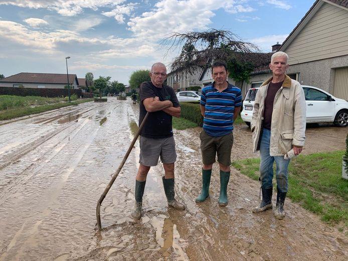 Buurtbewoners Luc Sents, Patrick De Valck en Herwig Van Nerum in hun straat, die herschapen is in een modderweg.