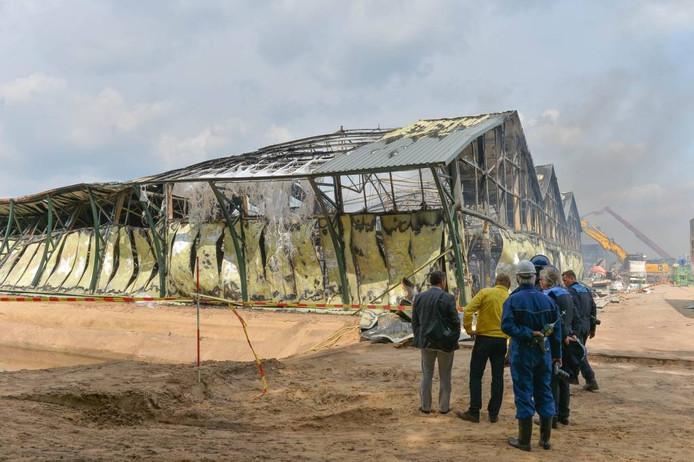 Fonteyn-eigenaar Dolf Nieland (gele blouse) bekijkt de schade aan zijn bedrijfspand.