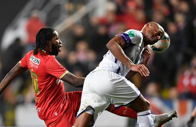 Vincent Kompany kopt de bal weg voor de aanstormende Antwerp-spits Dieumerci Mbokani. Beeld BELGA