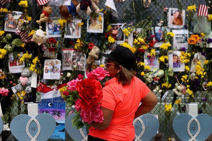 Aan het hek hangen bloemen en foto's van slachtoffers.