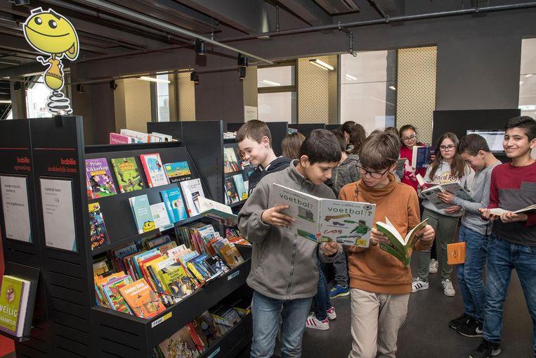 De kinderen snuisteren samen in de boeken op het Makkelijk Lezen Plein.