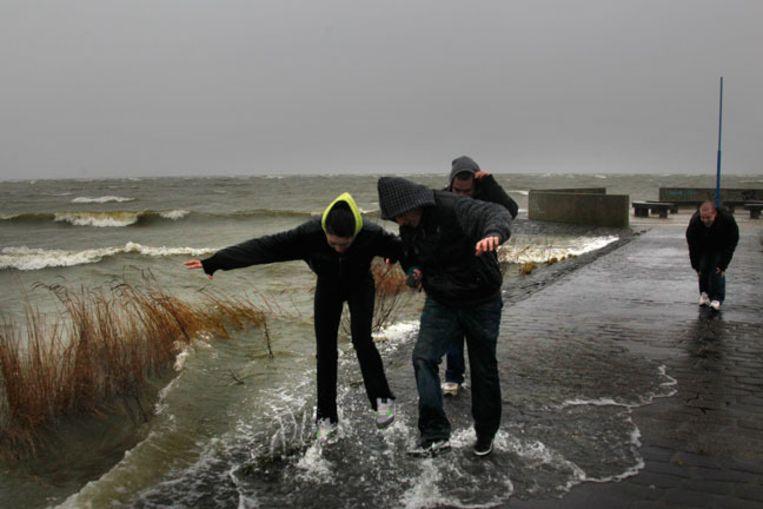 Jongeren trotseren de harde wind op de pier bij het Friese recreatiegebied Holle Poarte. © ANP Beeld