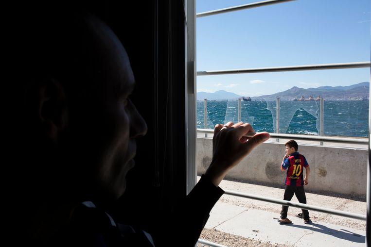 Murad kijkt uit het raam in het Griekse vluchtelingenkamp Skaramangas. Vandaag is hij terug in Irak. Beeld Johannes De Bruycker