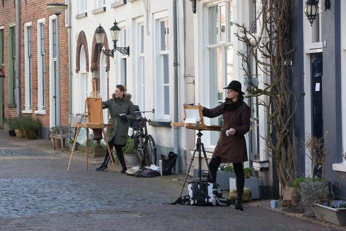 Wencke Vinks (op voorgrond) en Anouk Bijsterbosch schilderen oude gevels in het centrum van Doesburg.