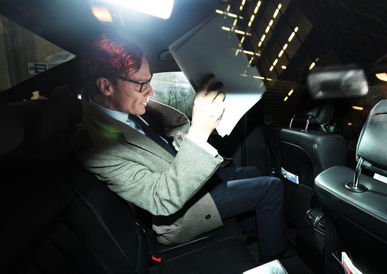 De voormalig CEO van Cambridge Analytica, Alexander Nix, wordt belaagd door de pers als hij zijn auto instapt. Beeld EPA