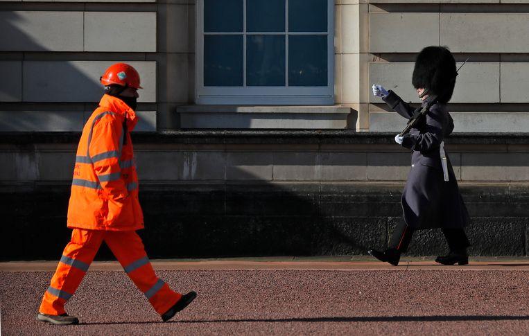 Een bewaker in Buckingham Palace patrouilleert terwijl een bouwer langsloopt in Londen. Beeld AP