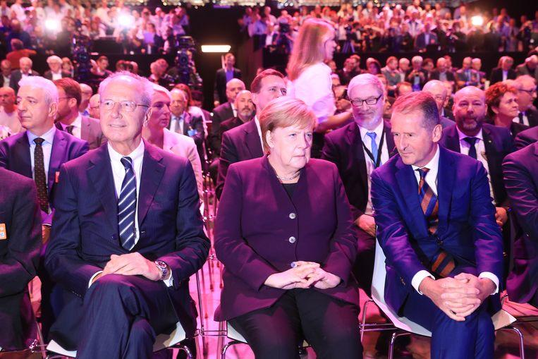 Herbert Diess en Hans Dieter Pötsch zitten naast Angela Merkel tijdens een ceremonie voor de lancering van een nieuwe elektrische auto. Beeld Bloomberg via Getty Images
