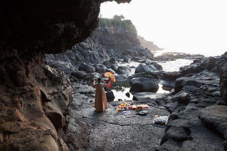 Een mudang, een Koreaanse sjamaan, bidt aan de kust van het eiland Jeju. De sjamanen bidden wisselend in de bergen en aan de kust om de natuurkrachten in balans te houden. Beeld EPA