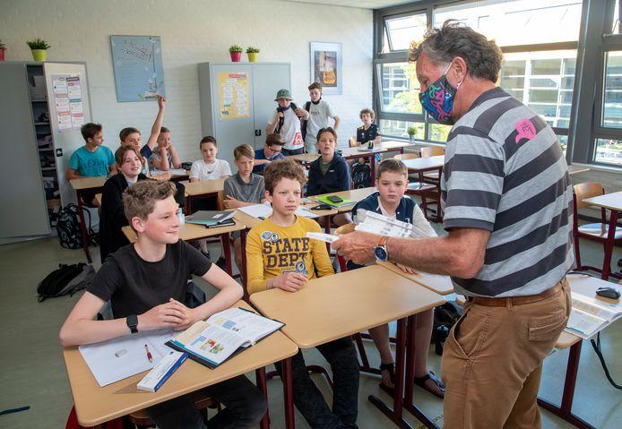 Docent Rein Tanis van het Christelijk College Groevenbeek deelt corona-zelftests uit aan leerlingen.