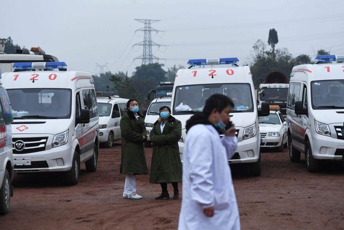 Reddingswerkers bij gereedstaande ambulances bij de Diaoshuidong kolenmijn in het zuidwesten van China, waar door een koolmonoxidelek zeker achttien mijnwerkers om het leven kwamen.