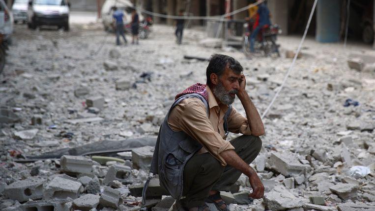 Een man zit tussen het puin van door regeringstroepen kapotgeschoten gebouwen in rebellengebied Douma, ten oosten van hoofdstad Damascus. Beeld AFP
