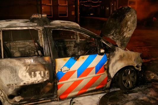 De politieauto die in brand werd gestoken.