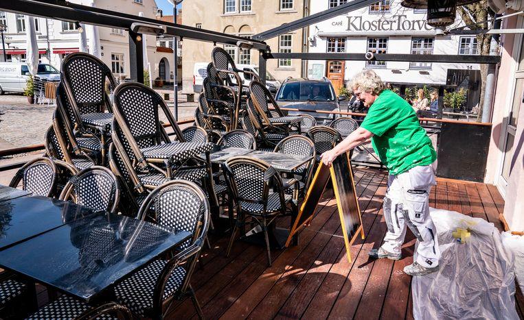 Het terras van een café in het Deense Aalborg wordt uitgestald. Vanaf 21 april mogen de restaurants in Denemarken, drie weken eerder dan gepland, weer open. Beeld EPA