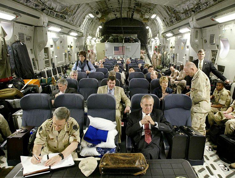 Rumsfeld (vooraan, tweede stoel van rechts) als minister van Defensie in 2003, na een bezoek aan een luchtmachtbasis in Saoedi-Arabië in 2003. Beeld Luke Frazza / AP