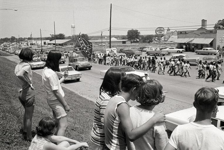 Blanke jongeren zien in Senatobia de Mississippi Freedom March passeren (1966). De Amerikaanse burgerrechtenbeweging inspireerde ook de Vlaamse studenten.  Beeld Bettmann Archive