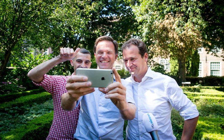 Mark Rutte maakt een selfie met Lodewijk Asscher en een jongen die een jointje rookte in het park. Beeld ANP