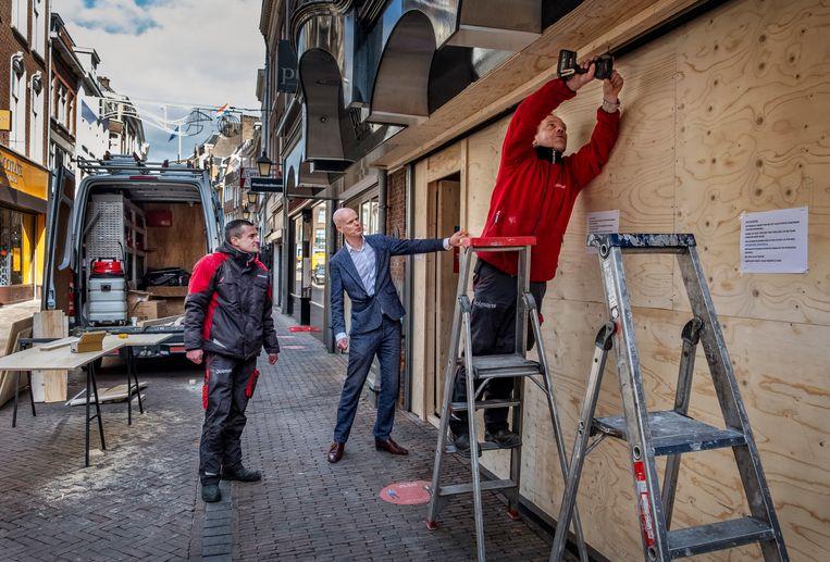 Ruud Reijers (midden) van juwelier Punte voor zijn pand in de Utrechtse Choorstraat dat wordt dichtgetimmerd nadat een plofkraak veel schade heeft aangericht.  Beeld Raymond Rutting / de Volkskrant