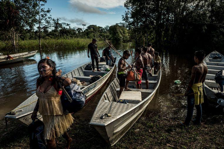 Leden van de Munduruku-stam komen toe in Caroçal Rio das Tropas, diep in het Amazonewoud in Brazilië.  Beeld NYT