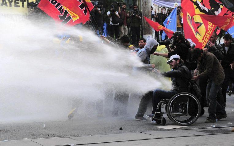 De politie zet het waterkanon in. Zelfs een gehandicapte man moet het ontgelden. Beeld REUTERS