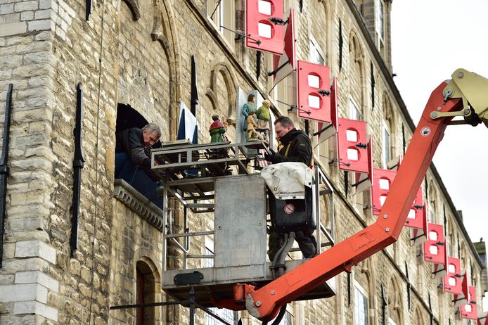 Toine Daelmans (l) en Ralf van Veghel demonteren het carillon aan de zijgevel van het stadhuis in Gouda. Het wordt de komende maanden gerestaureerd. Op 30 april moet het terug zijn. ,,Die tijd hebben we hard nodig.''